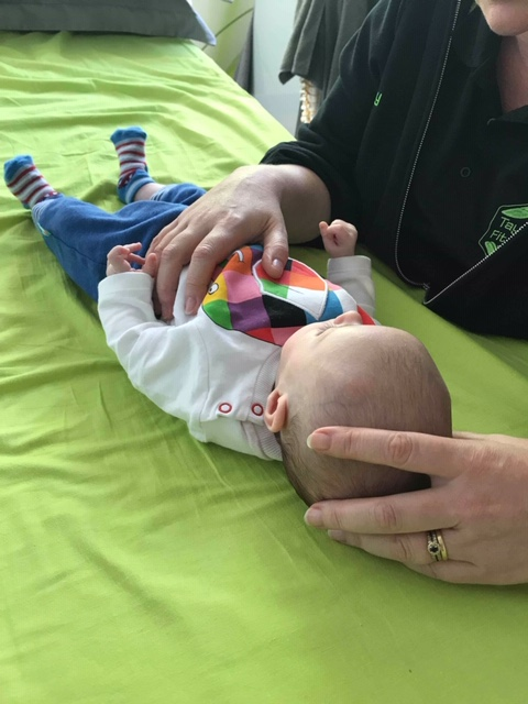 baby receiving a gentle craniosacral therapy treatment